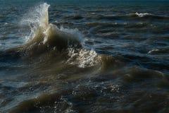 Παφλασμός των ωκεάνιων κυμάτων ενάντια στο σκηνικό του ήρεμου νερού στοκ εικόνες