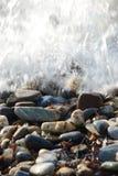 Παφλασμός νερού στη δύσκολη παραλία Στοκ Εικόνες
