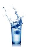 Παφλασμός στο ποτήρι του μπλε νερού με τον κύβο πάγου Στοκ φωτογραφία με δικαίωμα ελεύθερης χρήσης