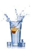 Παφλασμός στο ποτήρι του μπλε νερού με τον πορτοκαλή κύβο φετών και πάγου Στοκ φωτογραφία με δικαίωμα ελεύθερης χρήσης