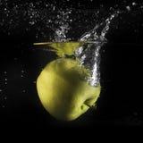 Παφλασμός της Apple στο νερό στο Μαύρο Στοκ Εικόνες