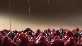 Παχιά αεριωθούμενα αεροπλάνα της υγρής πτώσης σοκολάτας στις κορυφές των φρέσκων φραουλών φιλμ μικρού μήκους