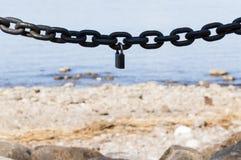 Παχιά αλυσίδα μετάλλων με μια κλειδαριά στο υπόβαθρο θάλασσας Στοκ Φωτογραφία