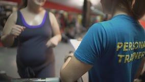 Παχιά γυναίκα που επιλύει στη γυμναστική με τον προσωπικό εκπαιδευτή, που ασκεί treadmill απόθεμα βίντεο