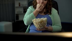 Παχιά γυναίκα που τρώει αλμυρό popcorn και που προσέχει τη TV, τεμπελιά, παθητικός τρόπος ζωής στοκ εικόνες