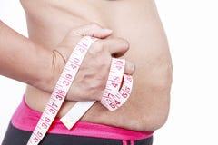 Παχιά γυναίκα που τσιμπά το λίπος της tummy στο άσπρο υπόβαθρο στοκ εικόνα