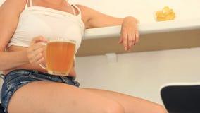 Παχιά μπύρα κατανάλωσης γυναικών Μια παχιά γυναίκα σε μια κοντή μπλούζα και τα σορτς πίνει την μπύρα με τα τσιπ στο φραγμό μπύρας απόθεμα βίντεο