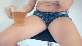 Παχιά μπύρα κατανάλωσης γυναικών Μια παχιά γυναίκα σε μια κοντή μπλούζα και τα σορτς πίνει την μπύρα με τα τσιπ στο φραγμό μπύρας φιλμ μικρού μήκους