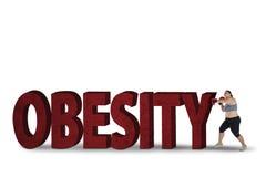 Παχιά πάλη γυναικών με τη λέξη παχυσαρκίας Στοκ εικόνες με δικαίωμα ελεύθερης χρήσης