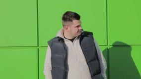 Παχιά τοποθέτηση ατόμων ενάντια σε έναν πράσινο τοίχο κοντά στο κατάστημα φιλμ μικρού μήκους