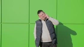 Παχιά τοποθέτηση ατόμων ενάντια σε έναν πράσινο τοίχο κοντά στο κατάστημα απόθεμα βίντεο