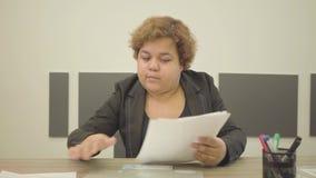 Παχουλή γυναίκα πορτρέτου στην επίσημη συνεδρίαση ένδυσης στον πίνακα στο γραφείο που κάνει την κινηματογράφηση σε πρώτο πλάνο γρ φιλμ μικρού μήκους