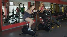 Παχουλή γυναίκα που εργάζεται σκληρά στο στάσιμο ποδήλατο για να επιτύχει τα αποτελέσματα, ικανότητα, αθλητισμός απόθεμα βίντεο