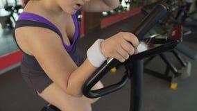 Παχουλό θηλυκό που εργάζεται σκληρά στο στάσιμο ποδήλατο στην αθλητική λέσχη, ικανότητα σωμάτων απόθεμα βίντεο
