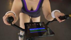 Παχουλό single-minded κορίτσι που εργάζεται σκληρά στο στάσιμο ποδήλατο στην αθλητική λέσχη, workout απόθεμα βίντεο