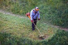 Παχύς βρώμικος εργαζόμενος ατόμων lawnmover τοπ άποψης που κόβει την ξηρά χλόη με το θεριστή χορτοταπήτων στοκ εικόνες