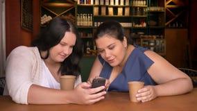 Παχύσαρκες καυκάσιες δύο φίλες που κοιτάζουν το smartphone και που συζητούν με τις συγκινήσεις με τα φλιτζάνια του καφέ απόθεμα βίντεο