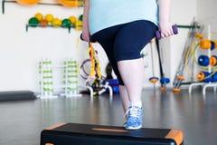 Παχύσαρκη γυναίκα που κάνει τη αερόμπικ βημάτων στοκ εικόνες