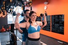 Παχύσαρκη γυναίκα που κάνει τις ασκήσεις με τα barbells με τη βοήθεια του εκπαιδευτή στοκ εικόνες με δικαίωμα ελεύθερης χρήσης