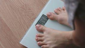 Παχύσαρκη γυναίκα που παίρνει στις κλίμακες για τον έλεγχο βάρους κατά τη διάρκεια της υγιεινής διατροφής, weightloss απόθεμα βίντεο