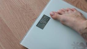 Παχύσαρκη γυναίκα που παίρνει στις κλίμακες για τον έλεγχο βάρους κατά τη διάρκεια της υγιεινής διατροφής, weightloss φιλμ μικρού μήκους
