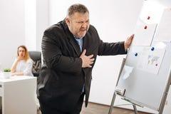 Παχύσαρκος εργαζόμενος που αισθάνεται τον ακραίο πόνο στο στήθος Στοκ εικόνες με δικαίωμα ελεύθερης χρήσης