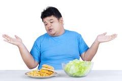 Παχύσαρκο άτομο με δύο είδη τροφίμων στοκ εικόνες