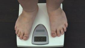Παχύσαρκο άτομο που μετρά το βάρος στις κλίμακες στο σπίτι, επιμορφωτικό πρόγραμμα αδυνατίσματος, υγεία απόθεμα βίντεο