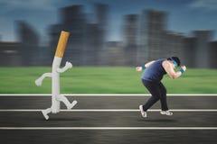 Παχύσαρκο άτομο που τρέχει μακρυά από ένα τσιγάρο Στοκ εικόνα με δικαίωμα ελεύθερης χρήσης