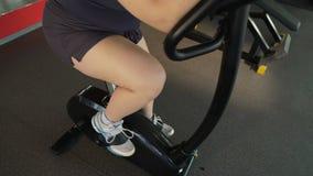 Παχύσαρκο γυναικών στο στάσιμο ποδήλατο στην αθλητική λέσχη, απώλεια βάρους workout φιλμ μικρού μήκους