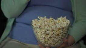 Παχύσαρκο θηλυκό με τη μεγάλη κοιλιά που τρώει τη μεγάλη μερίδα αλμυρό popcorn στον καναπέ απόθεμα βίντεο