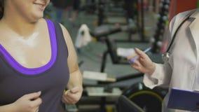 Παχύσαρκο κορίτσι που ασκεί treadmill στη γυμναστική, που μιλά στη νοσοκόμα κατά μέρος, ρολόι βάρους φιλμ μικρού μήκους