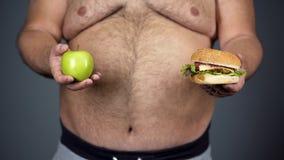 Παχύ άτομο που επιλέγει μεταξύ του μήλου και του χάμπουργκερ, που τηρούν την υγιεινή διατροφή, κινηματογράφηση σε πρώτο πλάνο στοκ εικόνες με δικαίωμα ελεύθερης χρήσης