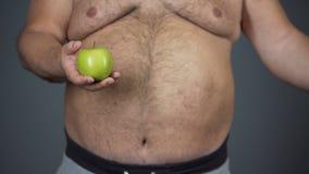 Παχύ άτομο που επιλέγει το μήλο αντί του χάμπουργκερ, που κρατά την υγιεινή διατροφή, κινηματογράφηση σε πρώτο πλάνο κοιλιών φιλμ μικρού μήκους