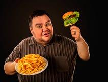 Παχύ άτομο που τρώει το γρήγορο φαγητό hamberger Πρόγευμα για το υπέρβαρο πρόσωπο Στοκ Φωτογραφία