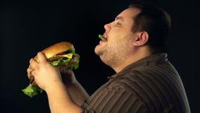 Παχύ άτομο που τρώει hamberger το γρήγορο φαγητό Πρόγευμα για το υπέρβαρο πρόσωπο φιλμ μικρού μήκους