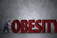 Παχύ άτομο που ωθεί μια λέξη παχυσαρκίας Στοκ εικόνα με δικαίωμα ελεύθερης χρήσης