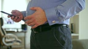 Παχύ άτομο στο πουκάμισο που κτυπά την κοιλιά και το smartphone χρήσης του φιλμ μικρού μήκους