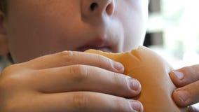 Παχύ αγόρι που τρώει cheeseburger την κινηματογράφηση σε πρώτο πλάνο προσώπου Ανθυγειινά τρόφιμα, γρήγορο φαγητό