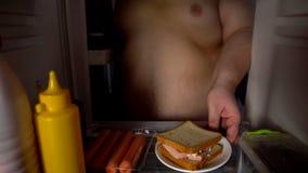 Παχύ αρσενικό παίρνοντας σάντουιτς από το ψυγείο, ανθυγειινή διατροφή, στατικός τρόπος ζωής στοκ εικόνα με δικαίωμα ελεύθερης χρήσης