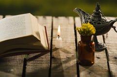 Παχύ βιβλίο που βρίσκεται ανοικτό στην ξύλινη επιφάνεια δίπλα στο μικρό καφετί μπουκάλι με τα κίτρινους λουλούδια και το λαμπτήρα Στοκ εικόνες με δικαίωμα ελεύθερης χρήσης