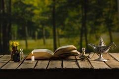 Παχύ βιβλίο που βρίσκεται ανοικτό στην ξύλινη επιφάνεια, μικρό καφετί μπουκάλι με τα λουλούδια, τους λαμπτήρες ύφους Aladin και τ Στοκ Φωτογραφία