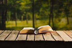 Παχύ βιβλίο που βρίσκεται ανοικτό στην ξύλινη επιφάνεια, ντεμοντέ συνεδρίαση επιτραπέζιων ρολογιών νύχτας δίπλα σε το, μαγικός βλ Στοκ φωτογραφία με δικαίωμα ελεύθερης χρήσης