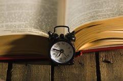 Παχύ βιβλίο που βρίσκεται ανοικτό στην ξύλινη επιφάνεια, ντεμοντέ συνεδρίαση επιτραπέζιων ρολογιών νύχτας δίπλα σε το, μαγικός βλ Στοκ εικόνες με δικαίωμα ελεύθερης χρήσης