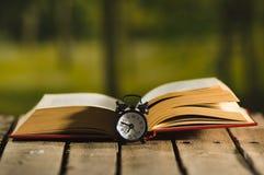 Παχύ βιβλίο που βρίσκεται ανοικτό στην ξύλινη επιφάνεια, ντεμοντέ συνεδρίαση επιτραπέζιων ρολογιών νύχτας δίπλα σε το, μαγικός βλ Στοκ Εικόνες