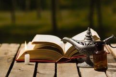 Παχύ βιβλίο που βρίσκεται ανοικτό στην ξύλινη επιφάνεια, το λαμπτήρα Aladin και τη συνεδρίαση κεριών κεριών δίπλα σε το, όμορφη ε Στοκ Εικόνα