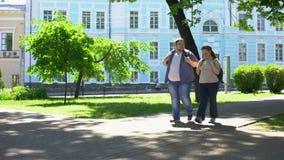 Παχύ ζεύγος σπουδαστών που περπατά στο πάρκο πόλεων, αστική ημερομηνία, ελεύθερος χρόνος, φιλία φιλμ μικρού μήκους