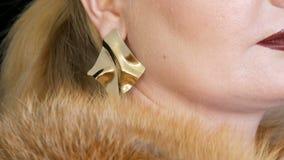 Παχύ θηλυκό πρότυπο με το χρυσό makeup και καπνώδη μάτια σε ένα παλτό της γούνας αλεπούδων και των μεγάλων χρυσών σκουλαρικιών πο απόθεμα βίντεο