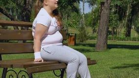 Παχύ κορίτσι που αισθάνεται τον πόνο στο στήθος που κοιτάζει γύρω για να ρωτήσει τη βοήθεια, κίνδυνος επίθεσης καρδιών απόθεμα βίντεο