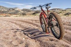 Παχύ ποδήλατο στο ίχνος με το βαθύ, χαλαρό αμμοχάλικο στοκ φωτογραφίες